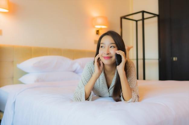 Женщина портрета красивая молодая азиатская на кровати с умным мобильным телефоном