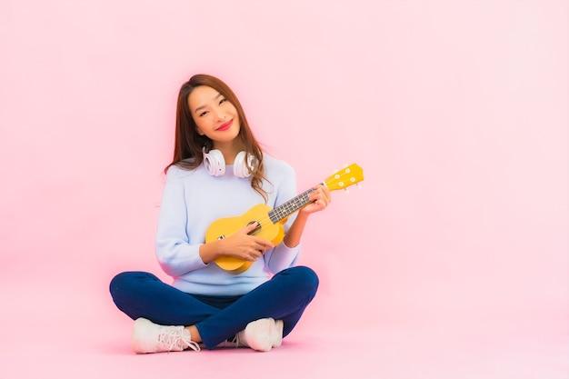 La bella giovane donna asiatica del ritratto gioca l'ukulele sulla parete isolata di colore rosa