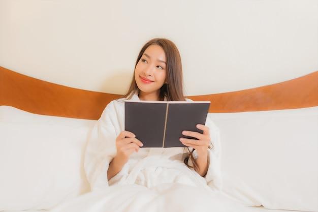 Bella giovane donna asiatica del ritratto che legge libro sul letto nell'interno della camera da letto