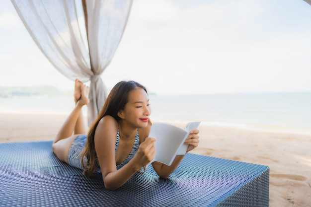 Portrait beautiful young asian woman reading book with happy smile relax in lounge bed chair on the beach sea ocean for leisure