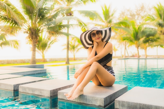 Portrait beautiful young asian woman relax around outdoor swimming pool in hotel resort with palm tree at sunset or sunrise
