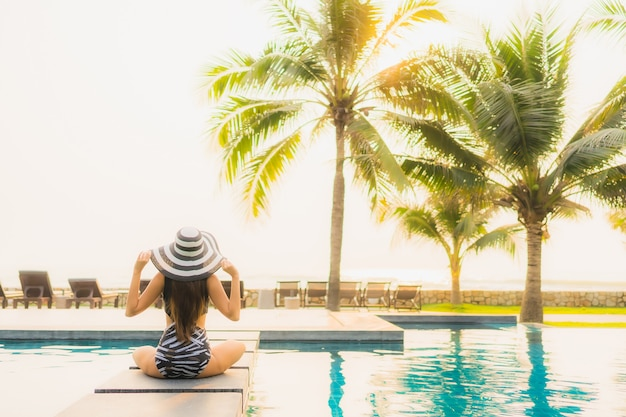 肖像画美しい若いアジアの女性は、夕日や日の出のヤシの木とホテルリゾートの屋外スイミングプールの周りでリラックスします。
