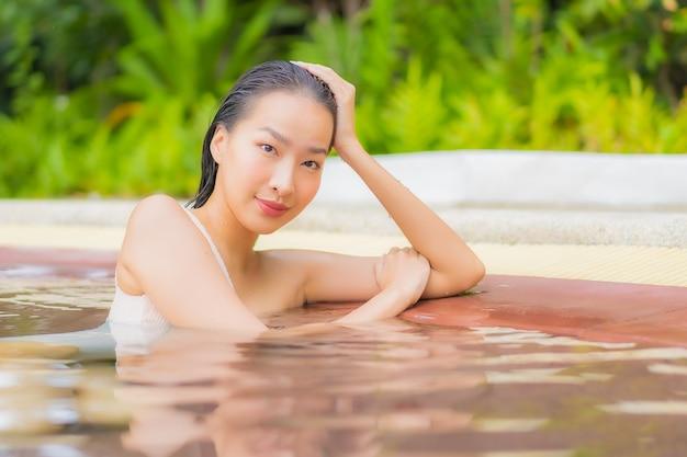 아름다운 젊은 아시아 여성의 초상화는 리조트의 야외 수영장 주변에서 휴식을 취합니다.