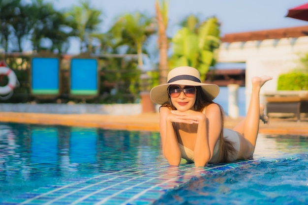 Portrait beautiful young asian woman relax around swimming pool in hotel resort