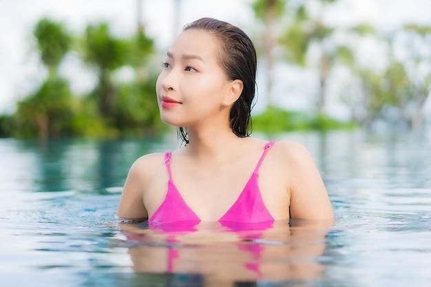 Женщина портрета красивая молодая азиатская ослабляет наслаждается вокруг открытого бассейна в отпуске