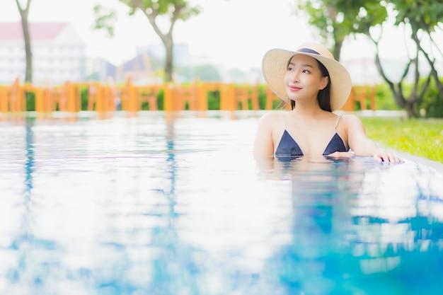 肖像画の美しい若いアジアの女性がリラックスしてレジャー休暇にホテルリゾートの屋外スイミングプールの周りの笑顔を楽しむ