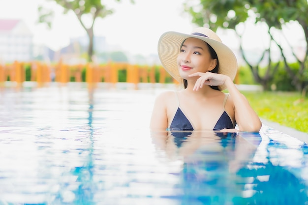 Женщина портрета красивая молодая азиатская ослабляет наслаждается улыбкой вокруг открытого бассейна в курорте гостиницы на каникулах отдыха