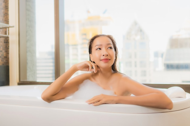 肖像画の美しい若いアジア女性はリラックスしてお楽しみくださいバスルームのインテリアでバスタブでお風呂に入る