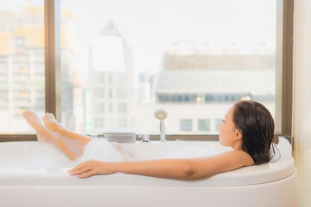 Женщина портрета красивая молодая азиатская ослабляет наслаждается принимать ванну в ванной в интерьере ванной комнаты