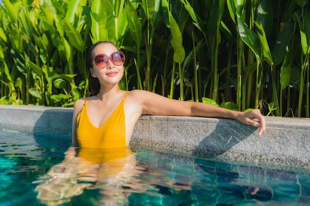 肖像画の美しい若いアジア女性はレジャー休暇のためのホテルリゾートの屋外スイミングプールの周りの幸せな笑顔をリラックスします。
