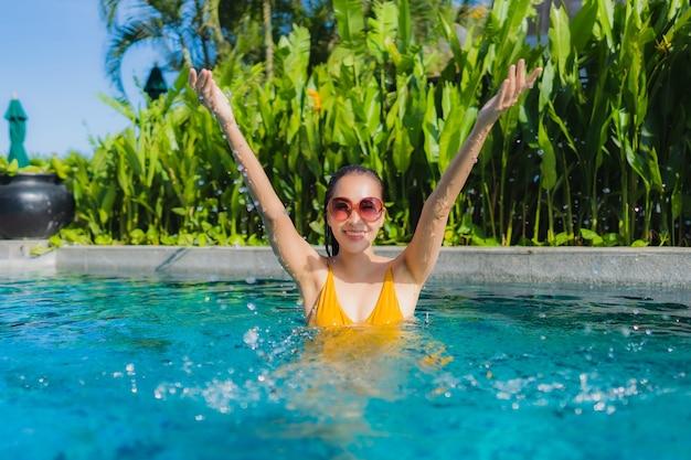 Женщина портрета красивая молодая азиатская ослабляет счастливую улыбку вокруг открытого бассейна в курорте гостиницы на отдыхе