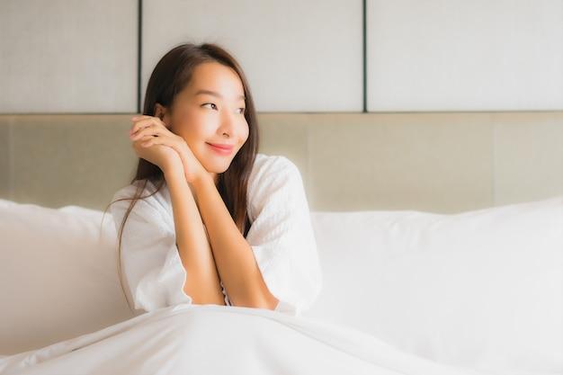 La bella giovane donna asiatica del ritratto si rilassa il sorriso felice in camera da letto