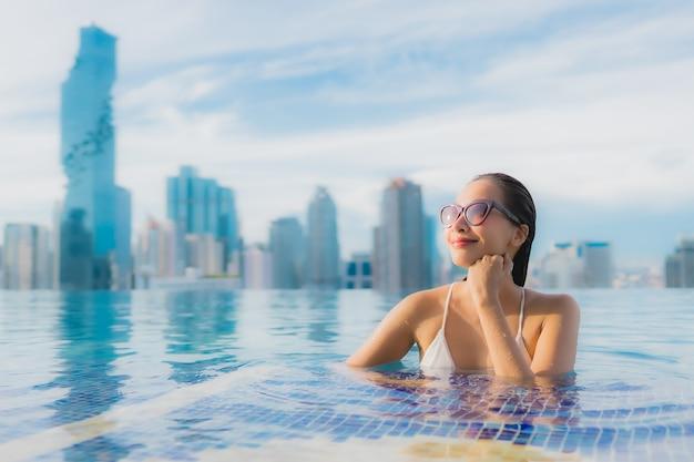 초상화 아름 다운 젊은 아시아 여자는 야외 수영장 주위에 행복한 미소 레저 휴식