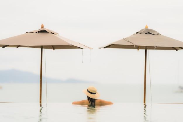 肖像画美しい若いアジア女性はホテルのリゾート地の高級屋外スイミングプールでほぼビーチ海海でリラックスします。