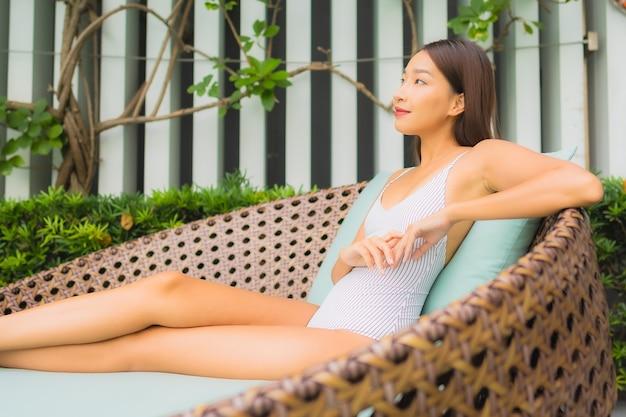 La bella giovane donna asiatica del ritratto si rilassa il tempo libero intorno alla piscina all'aperto nella località di soggiorno dell'hotel per le vacanze di viaggio