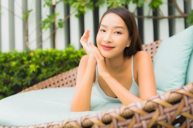 초상화 아름 다운 젊은 아시아 여자 여행 휴가를위한 호텔 리조트에서 야외 수영장 주변 레저 휴식