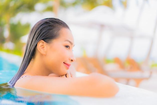 Женщина портрета красивая молодая азиатская ослабляет отдых вокруг открытого бассейна с пляжем океана моря