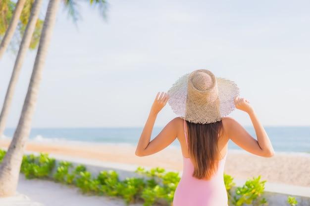 肖像画美しい若いアジアの女性は海と屋外スイミングプールの周りのレジャーをリラックス