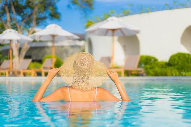 La bella giovane donna asiatica del ritratto si rilassa lo svago intorno alla piscina all'aperto con il mare