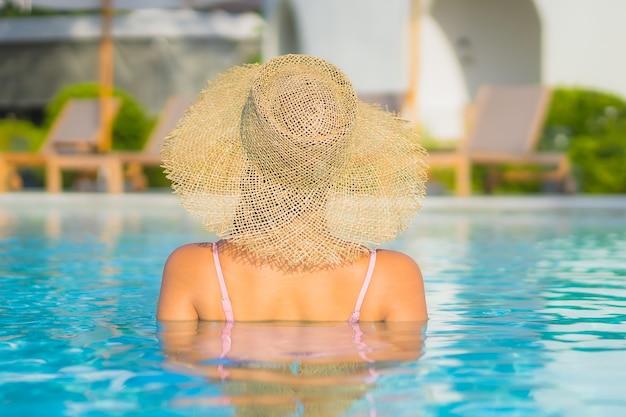 Женщина портрета красивая молодая азиатская ослабляет отдых вокруг открытого бассейна с морем