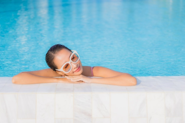 Portrait beautiful young asian woman relax leisure around outdoor swimming pool with sea