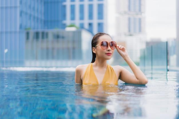Женщина портрета красивая молодая азиатская ослабляет отдых вокруг бассейна