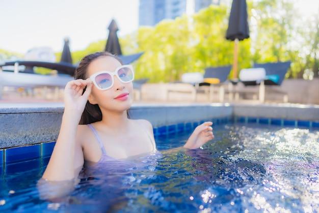 肖像画の美しい若いアジア女性リラックスレジャー屋外スイミングプールの周りを楽しむ