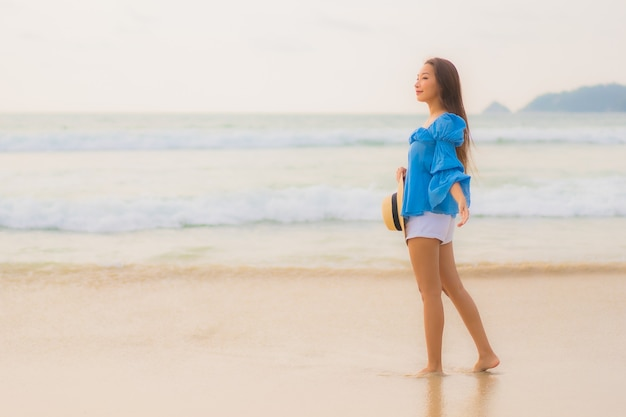 세로 아름 다운 젊은 아시아 여자는 일몰 시간에 해변 바다 바다 주위 여가 미소를 긴장