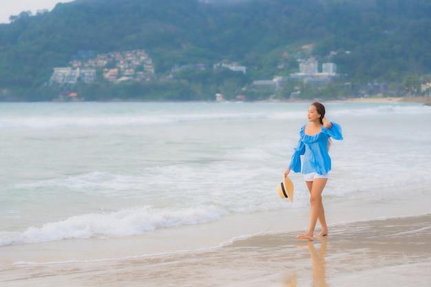La bella giovane donna asiatica del ritratto si rilassa il sorriso di svago intorno all'oceano del mare della spiaggia all'ora del tramonto