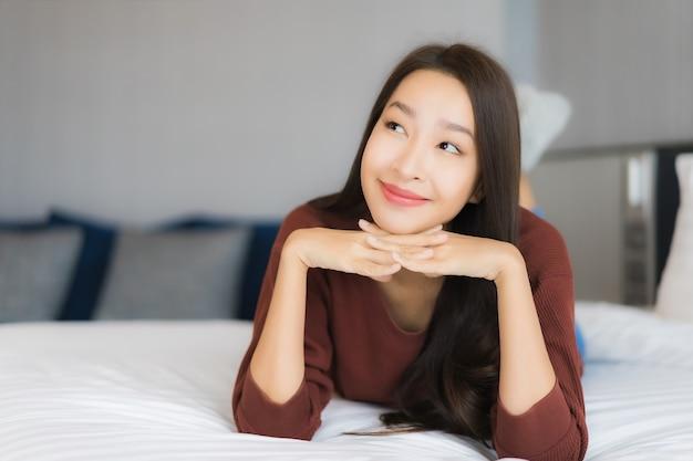肖像画の美しい若いアジア女性は寝室のインテリアでベッドでリラックスします。
