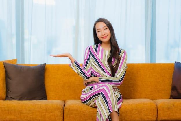 Женщина портрета красивая молодая азиатская ослабляет на софе в интерьере живущей комнаты