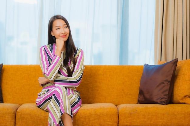 肖像画の美しい若いアジア女性はリビングルームのインテリアのソファーでリラックスします。