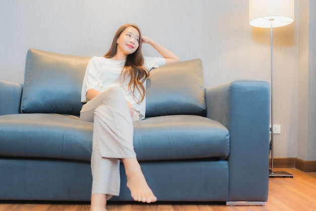 세로 아름 다운 젊은 아시아 여자 거실 인테리어에 소파에 휴식