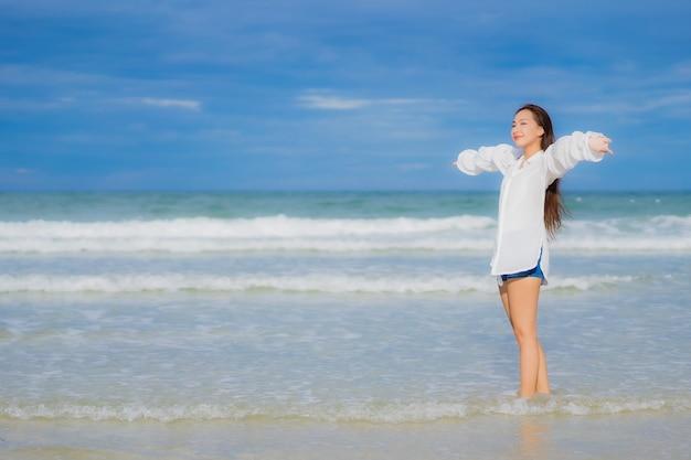 La bella giovane donna asiatica del ritratto si rilassa il sorriso intorno all'oceano del mare della spiaggia nel viaggio di viaggio di vacanza di festa