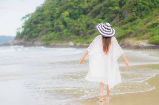 Portrait beautiful young asian woman relax smile around beach sea ocean in holiday vacation travel trip
