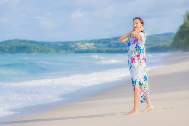 La bella giovane donna asiatica del ritratto si rilassa il sorriso intorno all'oceano del mare della spiaggia nella vacanza di festa