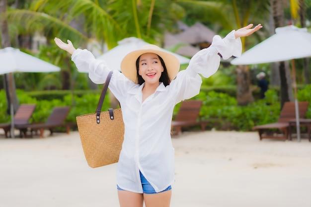 Женщина портрета красивая молодая азиатская ослабляет улыбку вокруг океана моря пляжа в поездке каникул праздника