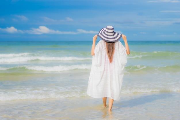 肖像画美しい若いアジアの女性は、休日の休暇旅行旅行でビーチの海の海の周りの笑顔をリラックス