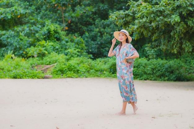 肖像画美しい若いアジアの女性は休日の休暇でビーチの海の海の周りの笑顔をリラックス