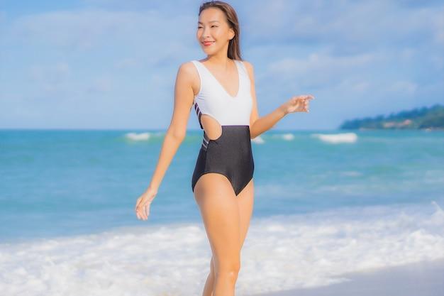 Женщина портрета красивая молодая азиатская ослабляет улыбку вокруг океана моря пляжа в отпуске