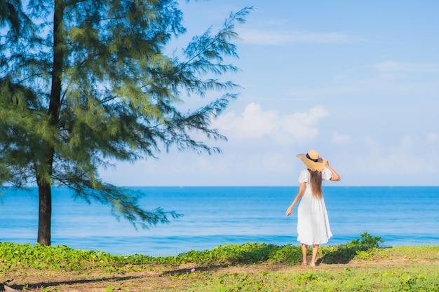 肖像画美しい若いアジアの女性は旅行休暇のための青い空と白い雲とビーチの海の海の周りの笑顔をリラックス