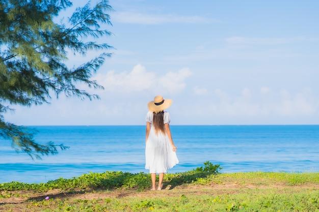 Женщина портрета красивая молодая азиатская ослабляет улыбку вокруг океана моря пляжа с облаком голубого неба белым для каникул перемещения