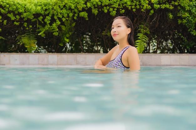 Женщина портрета красивая молодая азиатская ослабляет улыбку вокруг открытого бассейна для отдыха и каникул