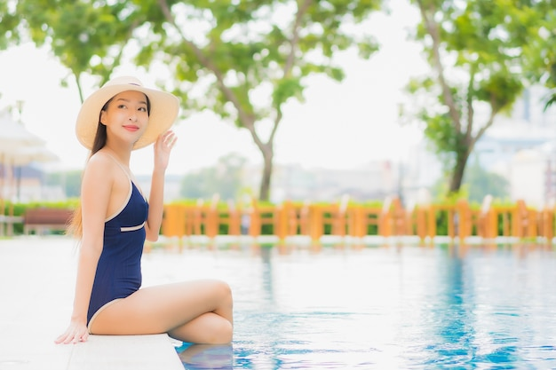 Portrait beautiful young asian woman relax smile around outdoor swimming pool in hotel resort in vacation travel