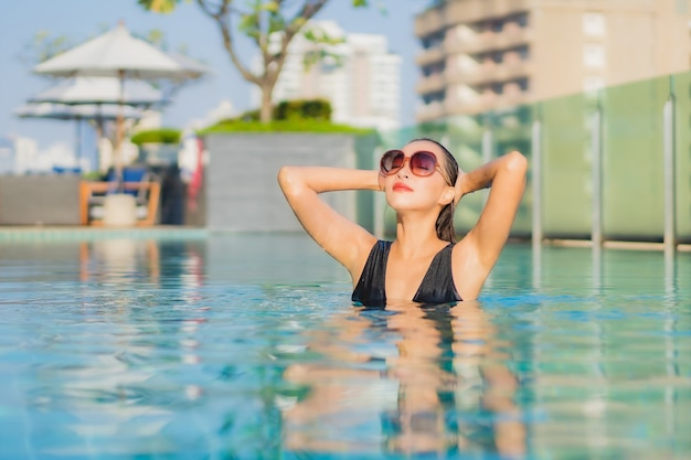 Portrait beautiful young asian woman relax smile around outdoor swimming pool in hotel resort
