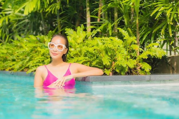 La bella giovane donna asiatica del ritratto si rilassa il sorriso intorno alla piscina all'aperto nella località di soggiorno dell'hotel