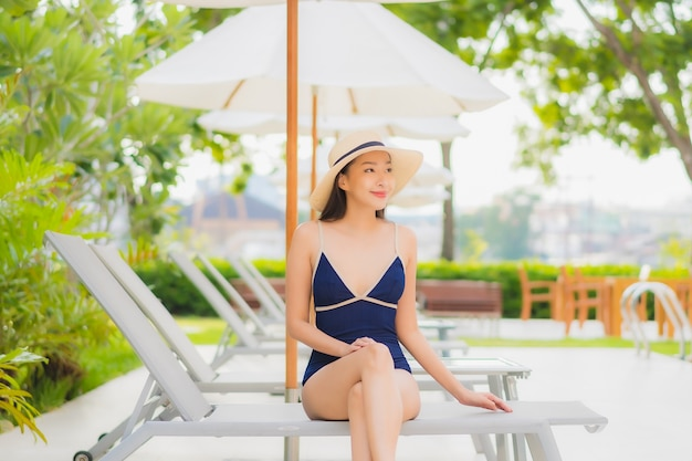 肖像画の美しい若いアジア女性は、休暇旅行でホテルリゾートの屋外スイミングプールの周りの笑顔をリラックスします。