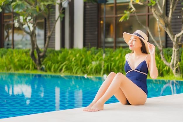 초상화 아름 다운 젊은 아시아 여자 휴가 여행에 호텔 리조트에서 야외 수영장 주위에 미소를 휴식