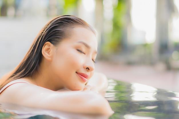 Женщина портрета красивая молодая азиатская ослабляет улыбку вокруг открытого бассейна в курорте гостиницы в путешествии каникул