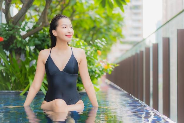 肖像画美しい若いアジアの女性がホテルリゾートの屋外スイミングプールの周りの笑顔をリラックス